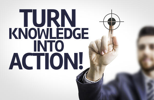 Business man pointing to transparent board with text Turn Knowledge Into Action!