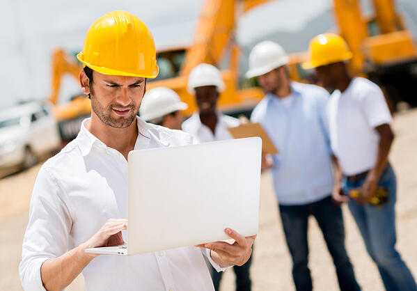 Male engineer at a construction site with a computer