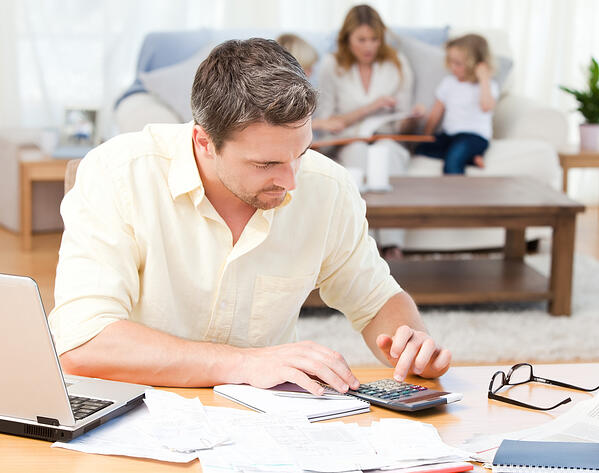 Man calculating his bills while his family are sitting on the sofa