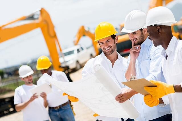 Group of architects and engineers at a building site looking at blueprints.jpeg