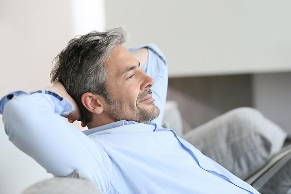 Middle-aged man having a restful moment relaxing in sofa