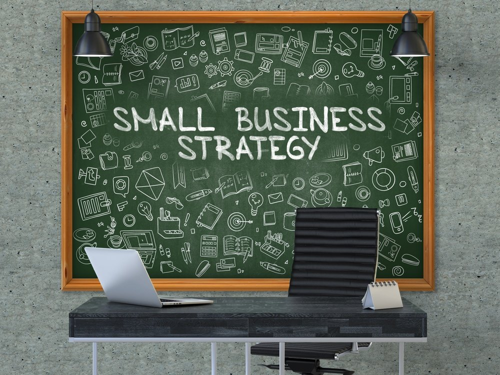Small Business Strategy. Green Chalkboard on the Gray Concrete Wall in the Interior of a Modern Office with Hand Drawn Small Business Strategy. Business Concept with Doodle Style Elements. 3D..jpeg